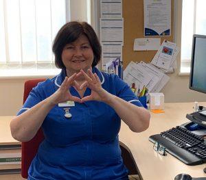 A Primrose Hospice nurse makes a heart shape using her hands.