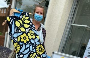 Primrose Hospice charity shop manager holding dress while wearing PPE