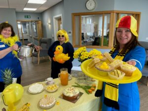 Primrose Hospice nurses dressed in yeloow feather boas, hats and wigs, hold a tea party to promote Yellow Week.