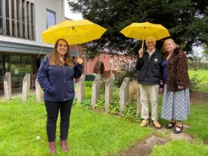 Lucy Perkins with Jim and Ruth Wood holding yellow umbrellas in the gardens of Primrose Hospice.