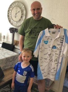 Leighton Webster with son Noahholding a Birmingham City football shirt signed by nurses from the hospital which cared for him at The Alexandra Hospital, Redditch.